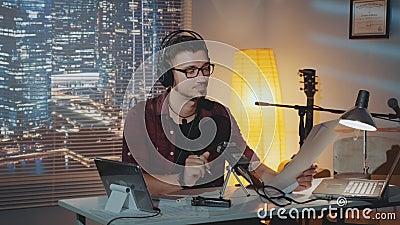 Οικιακό στούντιο ηχογράφησης: ο ομιλητής στο ακουστικό διαβάζει την ιστορία στο μικρόφωνο απόθεμα βίντεο