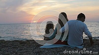 Οικογένεια με λίγη συνεδρίαση κορών κοντά στη θάλασσα απόθεμα βίντεο