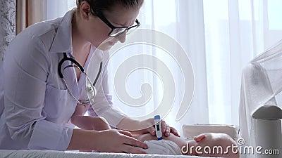 Οικογενειακός γιατρός, ιατρικός εργαζόμενος με τη θερμοκρασία μέτρων θερμομέτρων του σώματος μωρών απόθεμα βίντεο