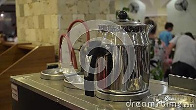 Οι άνθρωποι παίρνουν καυτές λαμπερές μεταλλικές τσαγιέρες με μαύρη λαβή σε εστιατόριο φιλμ μικρού μήκους
