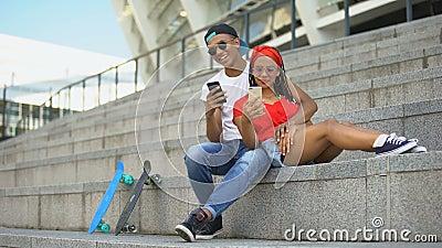 Οι έφηβοι που γελούν με κύλιση στα κοινωνικά δίκτυα σε smartphone και ψυχαγωγία απόθεμα βίντεο