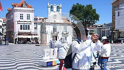 Οι ασιατικοί τουρίστες θέτουν για τις εικόνες στο κύριο τετράγωνο του Δημαρχείου του Κασκάις μια ηλιόλουστη ημέρα φιλμ μικρού μήκους