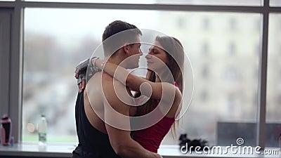 Οι εραστές εκφράζουν την αγάπη Το αρσενικό bodybuilder κρατά τη γυναίκα του στροβιλιμένος γύρω μαζί, το φίλημα και το αγκάλιασμα φιλμ μικρού μήκους