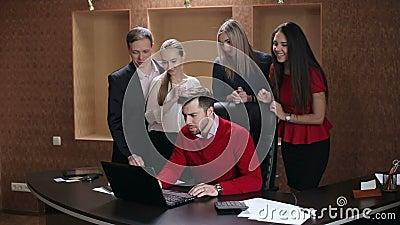 Οι ευτυχείς επιχειρηματίες γιορτάζουν την επιτυχία εξετάζοντας την οθόνη lap-top στο γραφείο απόθεμα βίντεο