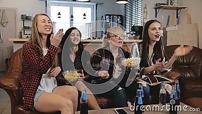 Οι θηλυκοί φίλοι προσέχουν τη TV παρουσιάζουν με τα πρόχειρα φαγητά στο σπίτι Νέα ευρωπαϊκά κορίτσια που απολαμβάνουν τη ρομαντικ φιλμ μικρού μήκους
