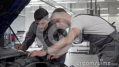 Οι μηχανικοί αυτοκινήτων συζητούν για το σπασμένο αυτοκίνητο στο γκαράζ τους κοιτώντας κάτω από το καπό απόθεμα βίντεο