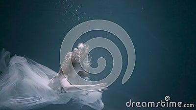 Οι νέες γυναίκες σε ένα λευκό ντύνουν την κολύμβηση κάτω από το νερό φιλμ μικρού μήκους