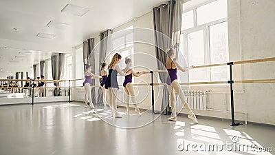 Οι νέοι χορευτές μπαλέτου ασκούν τις θέσεις ποδιών στο φραγμό μπαλέτου κάτω από την καθοδήγηση του επαγγελματικού ακριβούς δασκάλ απόθεμα βίντεο