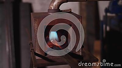 Οι φραγμοί μετάλλων σφυρηλατούν μέσα το φούρνο αερίου για τη θέρμανση στο σιδηρουργείο στο εργαστήριο εργοστασίων φιλμ μικρού μήκους