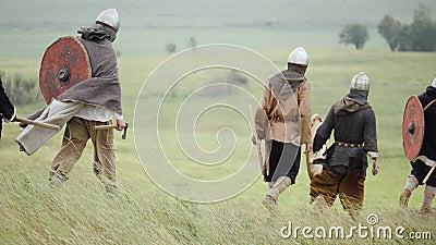 Ομάδα Βίκινγκ με τις ασπίδες που περπατούν προς τα εμπρός στο λιβάδι απόθεμα βίντεο