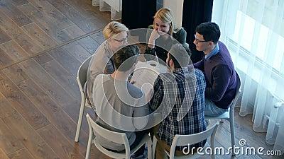 Ομαδική επικοινωνία, ομάδα πέντε ατόμων που συζητούν κάτι με χαμόγελο ενώ κάθονται στο τραπέζι του γραφείου απόθεμα βίντεο
