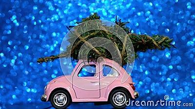 Ομσκ, Ρωσία - Oktober 27, 2018: Το πρότυπο αυτοκίνητο παιχνιδιών με το χριστουγεννιάτικο δέντρο επάνω στους γύρους στεγών σε μπλε απόθεμα βίντεο