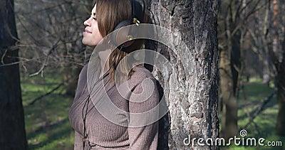 Ονειρεμένο όμορφο κορίτσι με ακουστικά που ακούει μουσική και απολαμβάνει τη φύση απόθεμα βίντεο