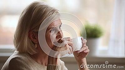 Ονειροπόλος ευτυχής μέση ηλικίας γυναίκα που φαίνεται καφές πρωινού μακριά κατανάλωσης απόθεμα βίντεο