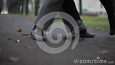 Ο άνδρας ` s και τα πόδια γυναικών ` s στα μαύρα παπούτσια δέρματος χορεύουν στο έδαφος που καλύπτεται από τα φύλλα απόθεμα βίντεο