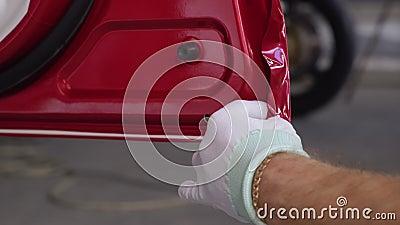 Ο άνθρωπος βάζει προστατευτική ταινία βινυλίου στην άκρη της πόρτας του αυτοκινήτου και ζεσταίνεται από τον ανεμιστήρα φιλμ μικρού μήκους