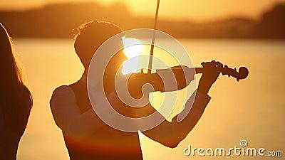Ο άνδρας και η γυναίκα ντουέτου βιολιών παίζουν το βιολί στη φύση στο ηλιοβασίλεμα στη λίμνη