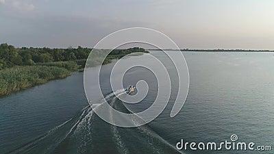 Ο αθλητής της κεραίας κρατά λαβή από σχοινί και κάνει βόλτες στην επιφάνεια του ποταμού κατά μήκος του ποταμού πίσω από ένα μηχαν φιλμ μικρού μήκους