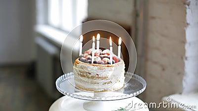 Ο αρχιμάγειρας κοριτσιών θέτει την πυρκαγιά στα κεριά στο κέικ σμέουρων βακκινίων φραουλών μιας των όμορφων κρέμας απόθεμα βίντεο