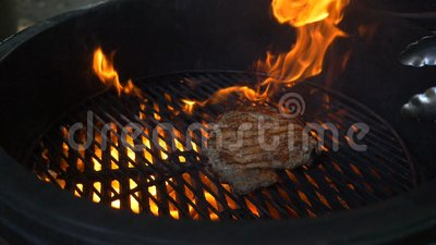 Ο αρχιμάγειρας μαγειρεύει τη juicy μεγάλη μπριζόλα κρέατος στη στρογγυλή σχάρα μέσω της οποίας η πυρκαγιά καίγεται απόθεμα βίντεο