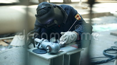 Ο βιομηχανικός εργάτης με τα προστατευτικά στοιχεία συγκόλλησης μασκών inox στις δομές χάλυβα κατασκευάζει το εργαστήριο απόθεμα βίντεο