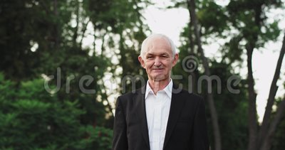 Ο γέρος παππούς κοιτάζει κατευθείαν στην κάμερα, στη φύση με ένα μαύρο κοστούμι χαμογελώντας λίγο φιλμ μικρού μήκους