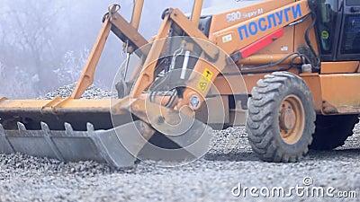 Ο εκσακαφέας διαδίδει το αμμοχάλικο στο έδαφος φιλμ μικρού μήκους