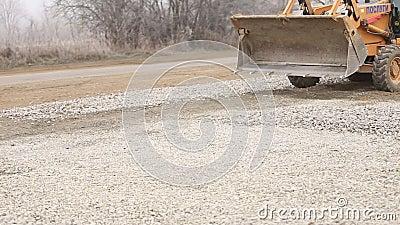 Ο εκσακαφέας διαδίδει το αμμοχάλικο στο έδαφος απόθεμα βίντεο