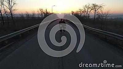 Ο εναέριος πυροβολισμός ως άνδρας και μια γυναίκα αγκαλιάζουν και πηγαίνουν στην πόλη στην αυγή, σε αργή κίνηση απόθεμα βίντεο