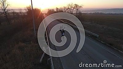 Ο εναέριος πυροβολισμός ως ζευγάρι των χορευτών εκτελεί την υποστήριξη που στέκεται στη μέση του δρόμου στην αυγή, σε αργή κίνηση απόθεμα βίντεο