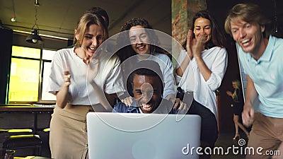Ο εργαζόμενος γραφείων ατόμων αφροαμερικάνων είναι συγκινημένος για τις καλές ειδήσεις, εξετάζει την οθόνη lap-top και γελώντας,  φιλμ μικρού μήκους
