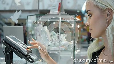 Ο ευτυχής πελάτης γυναικών σε ένα κατάστημα κοσμημάτων πληρώνει το τερματικό καρτών ανέπαφο φιλμ μικρού μήκους