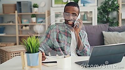 Ο εύθυμος αφροαμερικάνος freelancer μιλά στο κινητό τηλέφωνο και χρησιμοποιεί το lap-top που λειτουργεί στο σπίτι να κάνει την απ απόθεμα βίντεο