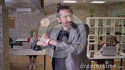 Ο εύθυμος επιχειρηματίας με τη γενειάδα χορεύει στην αρχή, χαμόγελο, οι συνάδελφοι προσέχουν σε τον, απασχολούνται στην έννοια, χ απόθεμα βίντεο