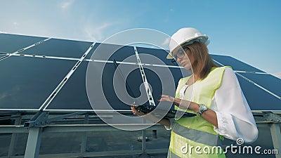 Ο θηλυκός κατασκευαστής περπατά κατά μήκος ενός ηλιακού πλαισίου με έναν υπολογιστή απόθεμα βίντεο