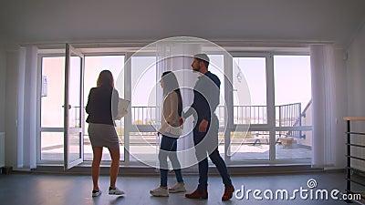 Ο θηλυκός καυκάσιος κτηματομεσίτης που παρουσιάζει το διαμέρισμα στο νέο καυκάσιο ζεύγος προσκαλεί για να προσέξει στο πεζούλι απόθεμα βίντεο