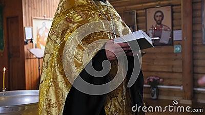 Ο ιερός πατέρας διαβάζει μια προσευχή στην εκκλησία πριν το τελετουργικό της βάπτισης Μεσαία βολή απόθεμα βίντεο