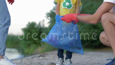 Ο καθαρισμός φιλανθρωπίας, νέα οικογένεια με το παιδάκι στα λαστιχένια γάντια συλλέγει τα απορρίματα στην τσάντα απορριμάτων στη  απόθεμα βίντεο