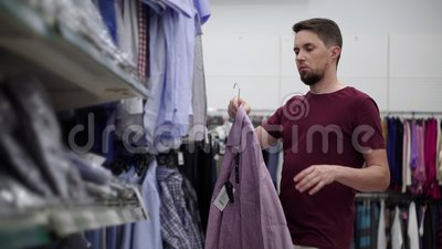 Ο καταναλωτής βλέπει μπλουζάκια στην περιοχή του καταστήματος ενδυμάτων φιλμ μικρού μήκους