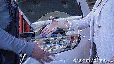 Ο καταναλωτής γυναικών δίνει τα κλειδιά αυτοκινήτων στον αυτόματο μηχανικό για την επισκευή και τινάζει τα χέρια στο πρατήριο βεν απόθεμα βίντεο
