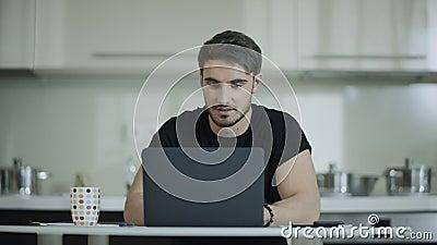 Ο λειτουργώντας φορητός προσωπικός υπολογιστής επιχειρησιακών ατόμων και πίνει την κουζίνα τσαγιού στο σπίτι φιλμ μικρού μήκους