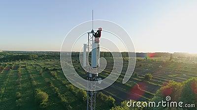 Ο μηχανικός με τη συσκευή σύνδεσε μια κινητή επικοινωνία για το ραδιο πύργο τηλεπικοινωνιών στο υπόβαθρο του μπλε ουρανού με φιλμ μικρού μήκους