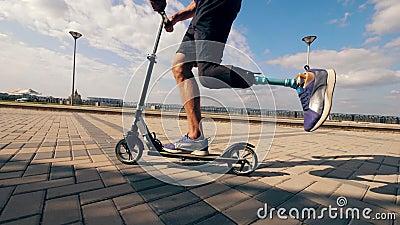 Ο σκούτερ οδηγείται από έναν άντρα με βιονικό πόδι σε αργή κίνηση φιλμ μικρού μήκους