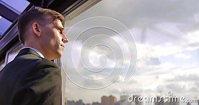 Ο σοβαρός επιτυχής αρσενικός επιχειρηματίας στέκεται στο γραφείο κοντά στο παράθυρο και απολαμβάνει το πανόραμα στο ηλιοβασίλεμα απόθεμα βίντεο
