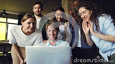 Ο συγκινημένος νεαρός άνδρας εξετάζει την οθόνη lap-top, και εκφράζοντας την ευτυχία, οι συνάδελφοί του τον συγχαίρουν απόθεμα βίντεο