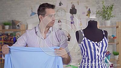 Ο σχεδιαστής μόδας εργάζεται με ύφασμα και προσαρμόζεται σε ένα μανεκέν κοντά φιλμ μικρού μήκους
