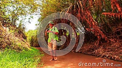 Ο τουρίστας περπατά τις ξυπόλυτες φωτογραφίες στα ρηχά νερά νεράιδα-ρευμάτων φιλμ μικρού μήκους