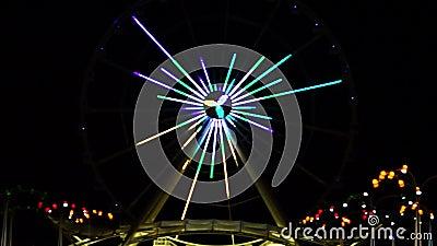 Ο τροχός του λούνα παρκ τρέχει τη νύχτα, φωτισμένος από τα φώτα, με πολύχρωμα τρεχούμενα φώτα στο μεγάλο καρουσέλ απόθεμα βίντεο