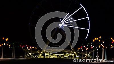 Ο τροχός του λούνα παρκ τρέχει τη νύχτα, φωτισμένος από τα φώτα, με πολύχρωμα τρεχούμενα φώτα στο μεγάλο καρουσέλ φιλμ μικρού μήκους