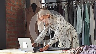 Ο όμορφος σχεδιαστής μόδας κοιτάζει το φορητό υπολογιστή και χαμογελά φιλμ μικρού μήκους